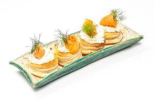 na białym tle widoczna jest prostokątna, recznie wykonana przez Stara Piekarnię, patera. Na paterze umieszczone są 4 pięknie wyglądające wytrawne ciastka francuskie z białym serkiem i łososiem